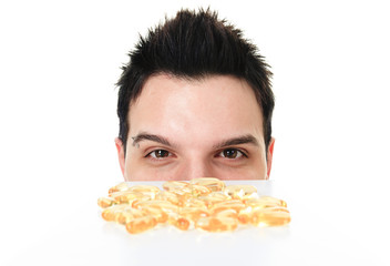 A young man is eating a omega-3 pill
