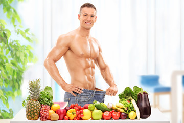 Attractive male posing behind a table with vegetables