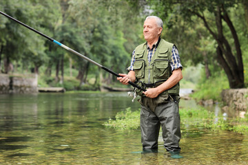 Cheerful mature fisherman fishing in a river