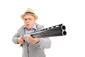 Furious senior man holding a shotgun