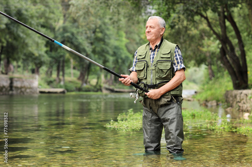 Cheerful mature fisherman fishing in a river - 77698382