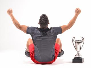 Deportista celebrando el triunfo con un trofeo.