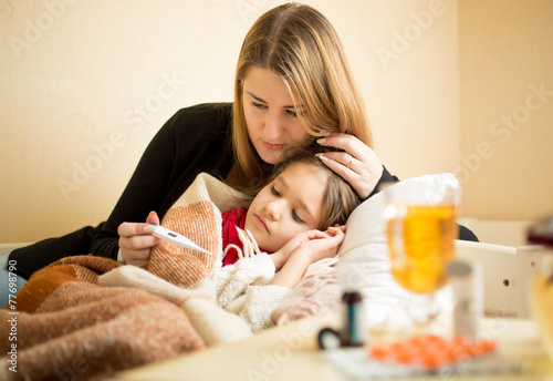 mother checking temperature of sick daughter lying in bed - 77698790