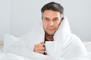 Mature Sick Man Holding Cup Of Coffee