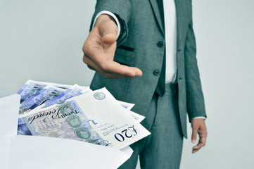 man taking an envelope full of pound sterling bills
