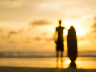 Silhouette of a surfer at sunset - intentional lens blur