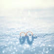 Wedding concept - two gold rings on the snow in winter day - 77701552