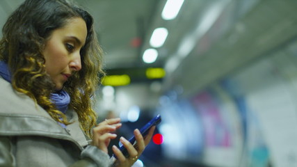 Attractive young woman using her phone as a train approaches
