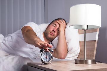 Man Snoozing Alarm Clock