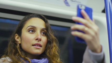 Attractive young woman takes a photo of herself on a train