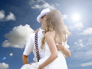 Attractive young couple about to kiss against blue sky