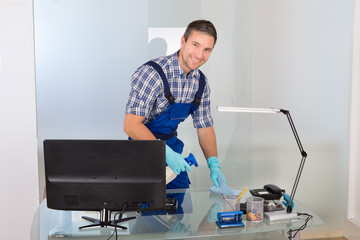 Male Janitor Cleaning Desk