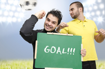 Man with empty blackboard cheering for scored goal