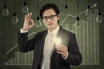 Businessman holding lightbulb with upward graph 1