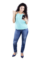 Cheerful girl with curly hair holding cellphone