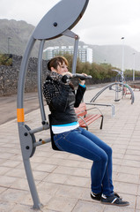 Junge Frau auf Fitnessgerät an Strandpromenade