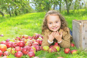 Cute little preschooler girl eating an apple on beautiful autumn