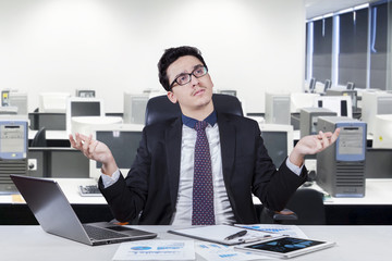 Confused man working at office