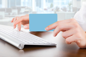 Female hands typing on white computer keyboard in office and giv