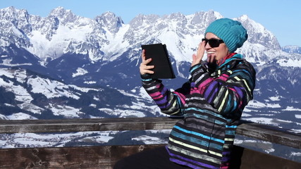 Young woman video chatting in the mountains, Alps