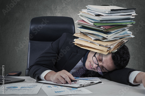 Exhausted man sleeping with paperwork - 77710973