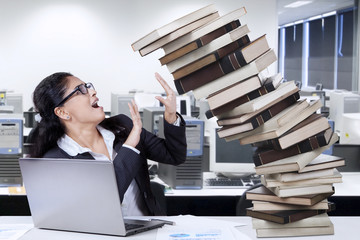 Indian employee with books in office