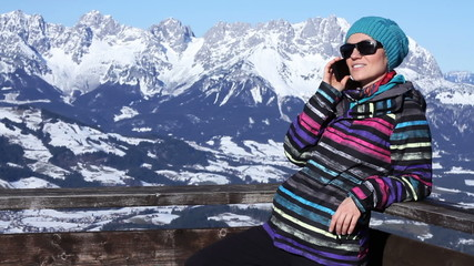Attractive woman talking on cellphone in the mountains, Alps