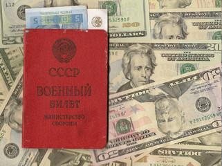 Военный билет с рублем и гривной на фоне долларов США