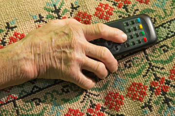 hand of old woman with TV driver
