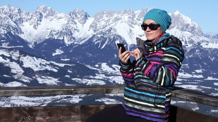 Attractive woman texting with her phone in the mountains, Alps