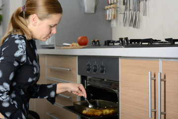 Woman cooks potatoes in the oven