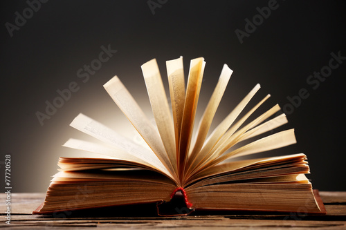 Open book with light over dark background - 77720528