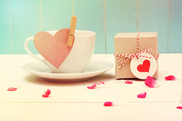 Coffee cup with heart tag and a small giftbox