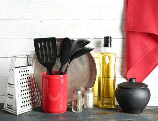 Plastic kitchen utensils in red cup with bottle of olive oil