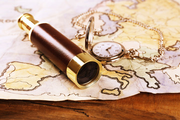 Spyglass, pocket watch and world map on wooden table background