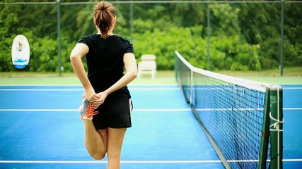 Woman stretching her Legs before game inside Tennis court