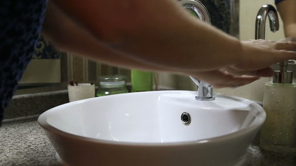 Woman washing hands in bathroom