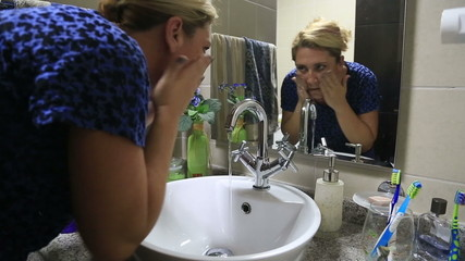 Woman washing her face with soap under running water