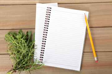 Blank notebook and pencil with a bunch of herbs