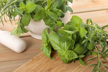 Fresh herbs with a mortar and pestle on a wooden worktop
