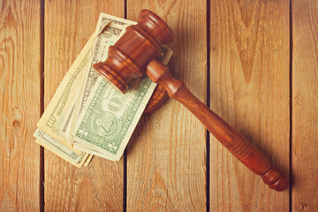 Judge gavel and money on wooden vintage background