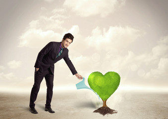 Business man watering heart shaped green tree