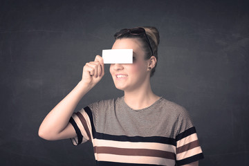 Pretty girl holding blank copy space paper at her eyes