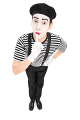 Mime artist holding a finger on his lips