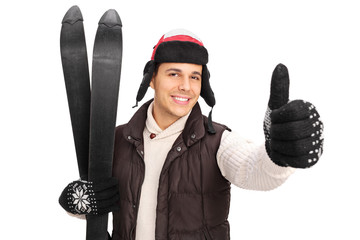 Young man posing with a pair of skis