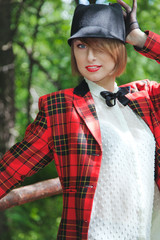 Beautiful young woman in horsewoman suit walks in forest
