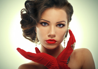Glamour girl in red gloves holding hands near face.