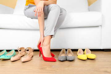 Trying on shoes by elegant lady sitting on white sofa