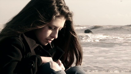 thoughtful female teenager sitting on the beach in cold winter