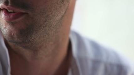 young unshaven man in white shirt speaking closeup